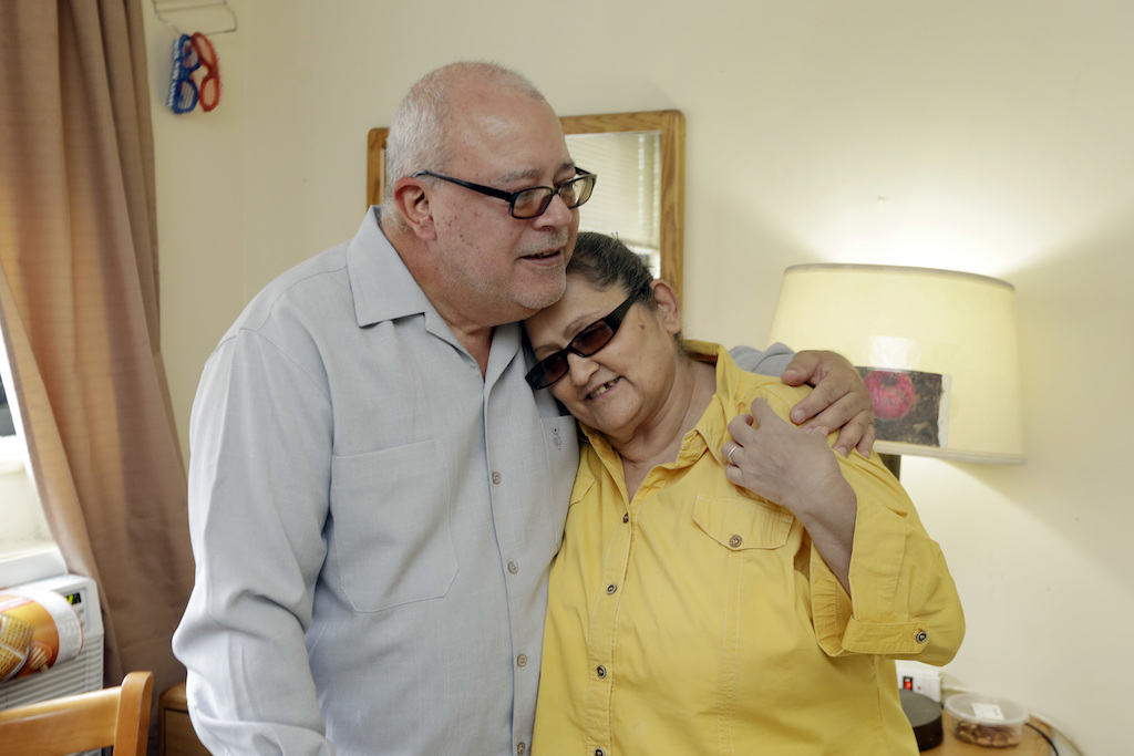 In this Friday, June 17, 2016, photo, Carmen Ramirez, and her husband, Ricardo Ramirez, embrace in their room at the Bronxwood Home for the Aged, in the Bronx borough of New York. A series of emergency expenses were enough to cost Carmen and Ricardo Ramirez their one-bedroom condominium in Washington Heights, a neighborhood close to the northern tip of Manhattan. Now a couple entering their golden years is out of their home and in an assisted-living facility. (AP Photo/Richard Drew)